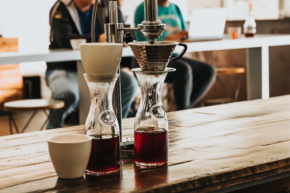 dwie karafki z filtrami i kawą oraz jedna biała filiżanka stojące na blacie
