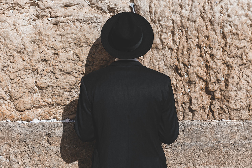 A Jewish man wearing a black hat and coat leaning on the Western Wall