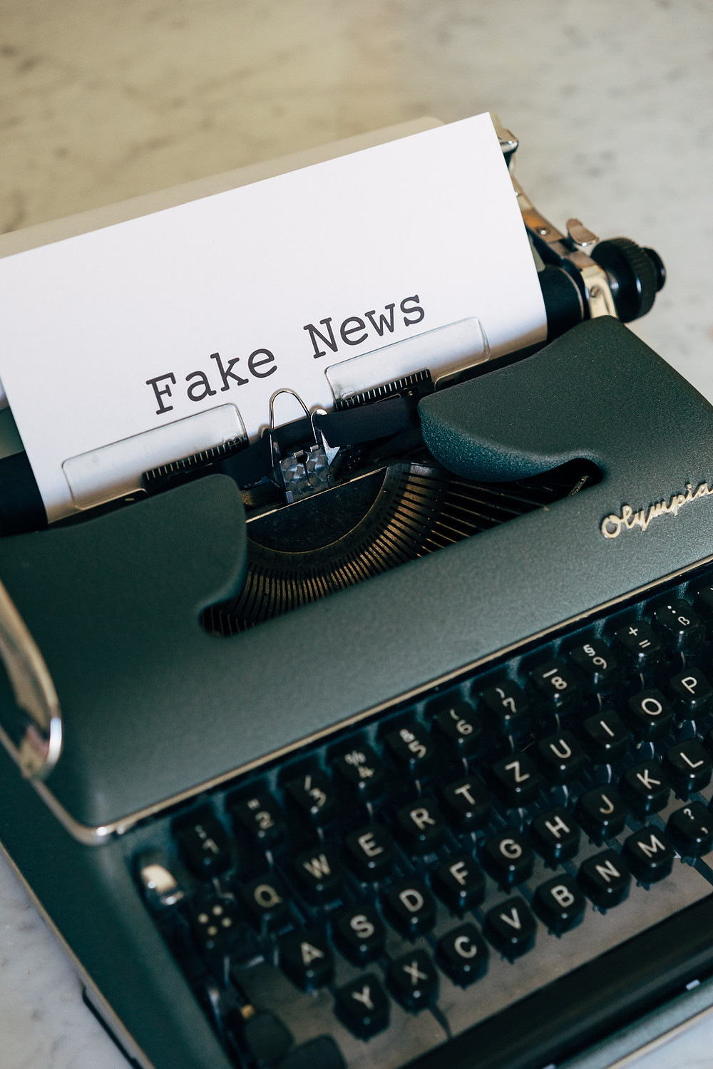 "A typewriter with a piece of paper in it that says ""Fake News."""