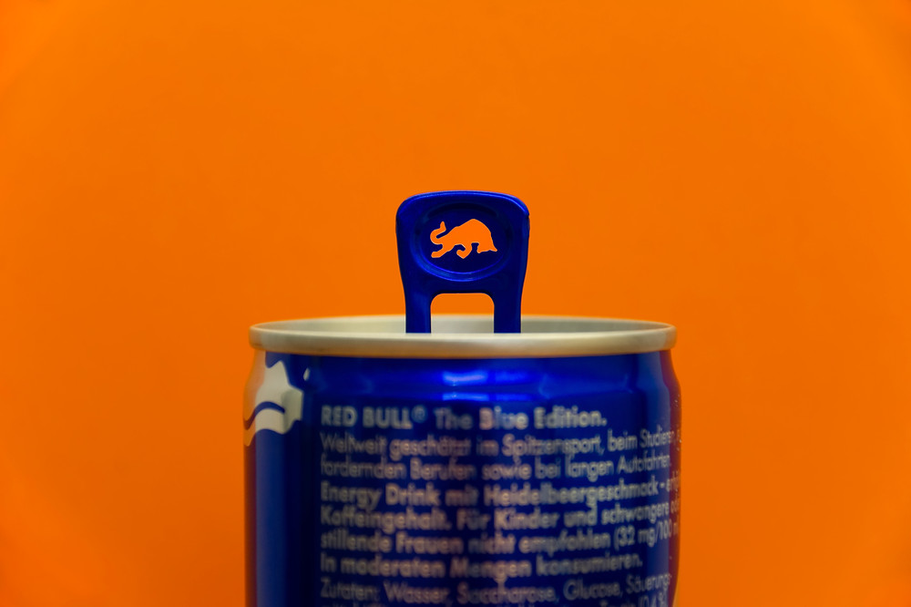 A picture of the top half of a can of red bull drink against an orange background