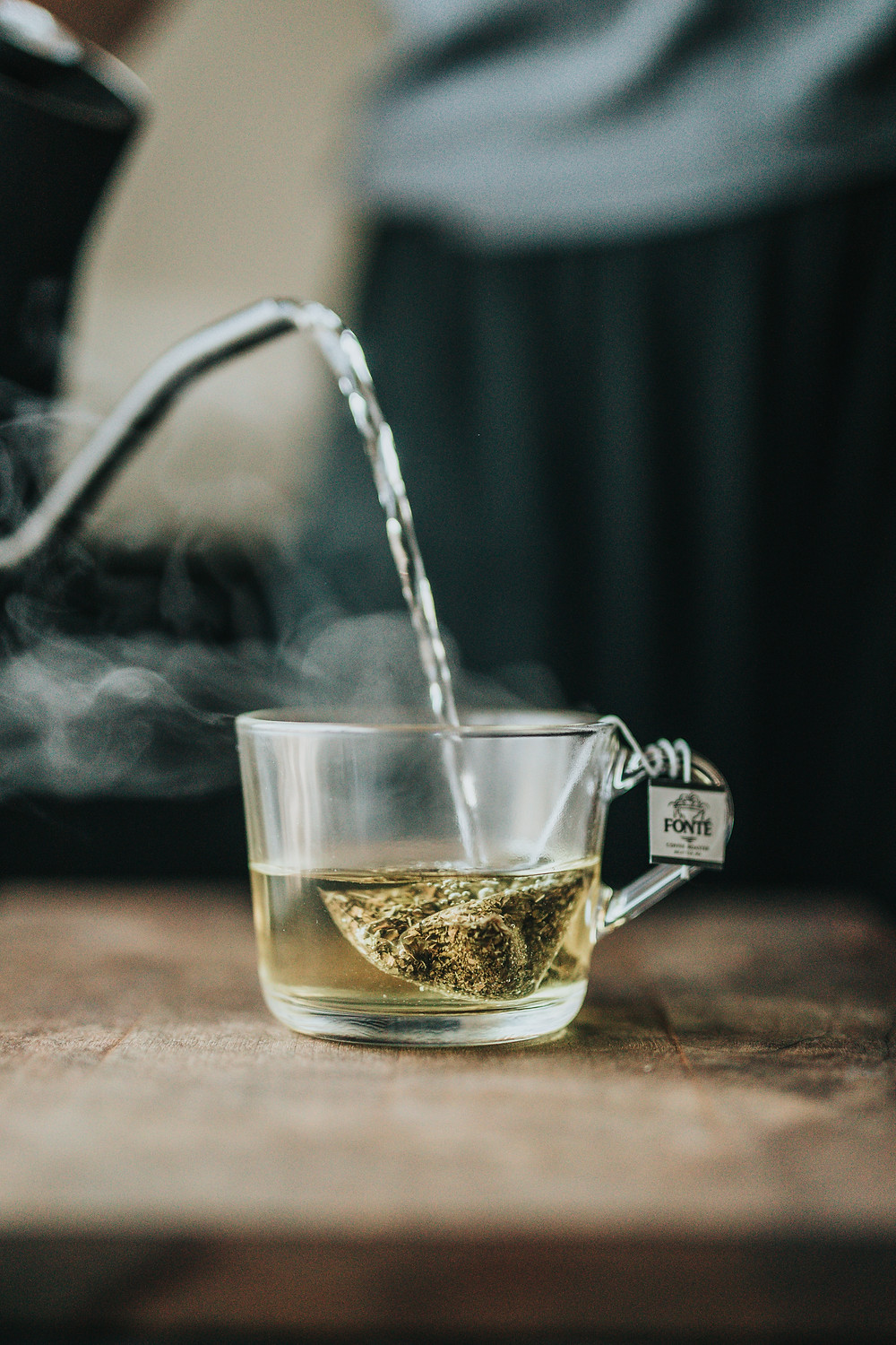 water pouring on a green tea bag in a glass mug