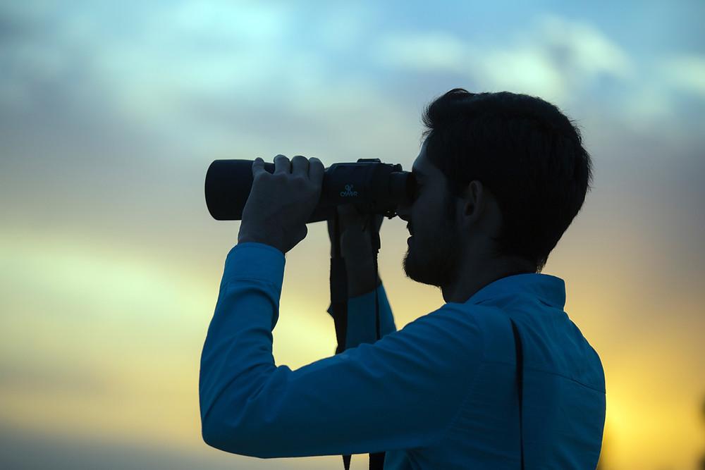 Mann mit Fernglas blickt in Sonnenuntergang.