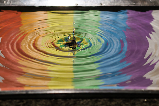 Water dropping into a pool of water, creating ripples, with a reflection of a rainbow