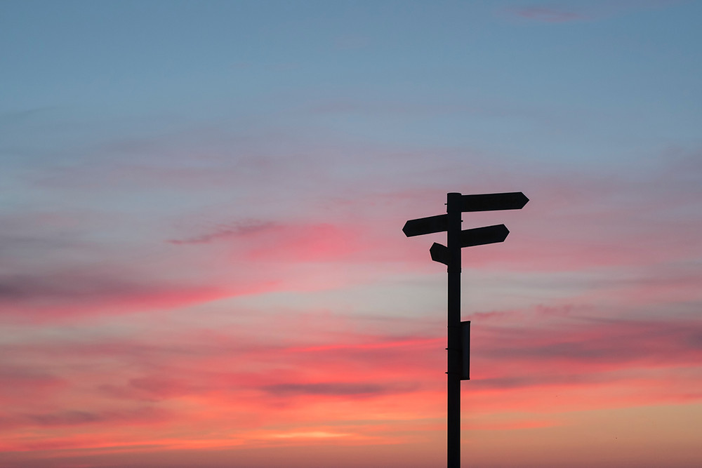 Silhouette of sign post with sunset sky