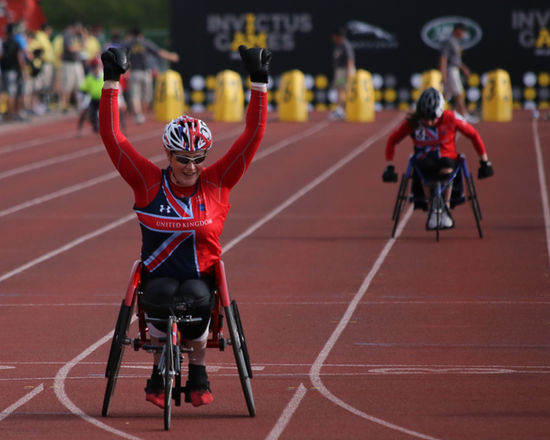 Wheelchair Racing in the Paralympic Games. A United Kingdom Paralympic athlete in a wheelchair (wearing a helmet and red sports shirt with the blue, white and red national flag on it) is celebrating their finish.