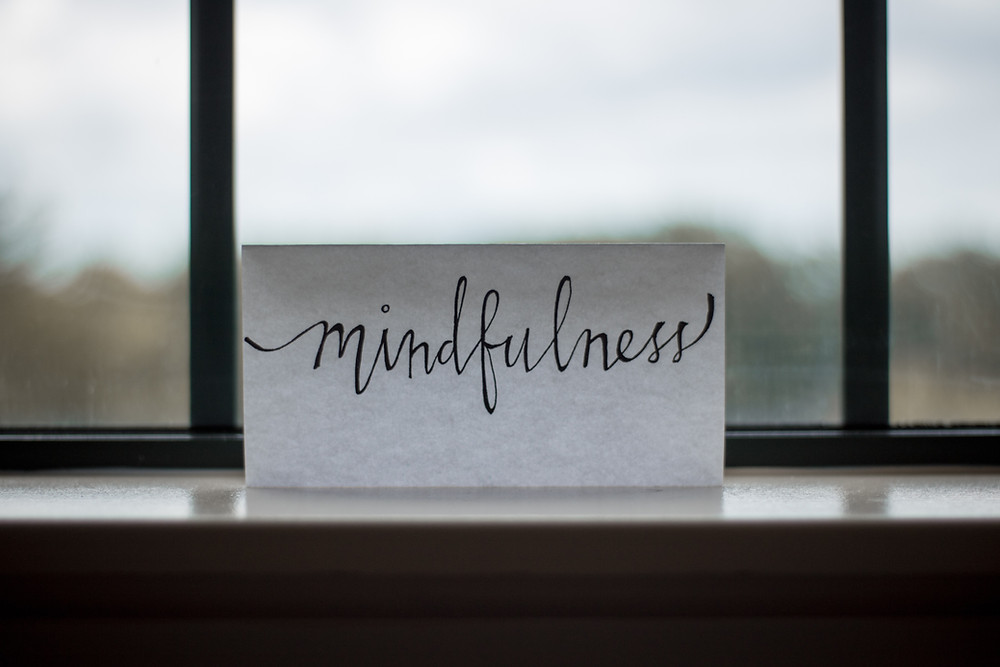 a card reading the handwritten word mindfulness placed on a window sill facing out to a blurred outdoor setting
