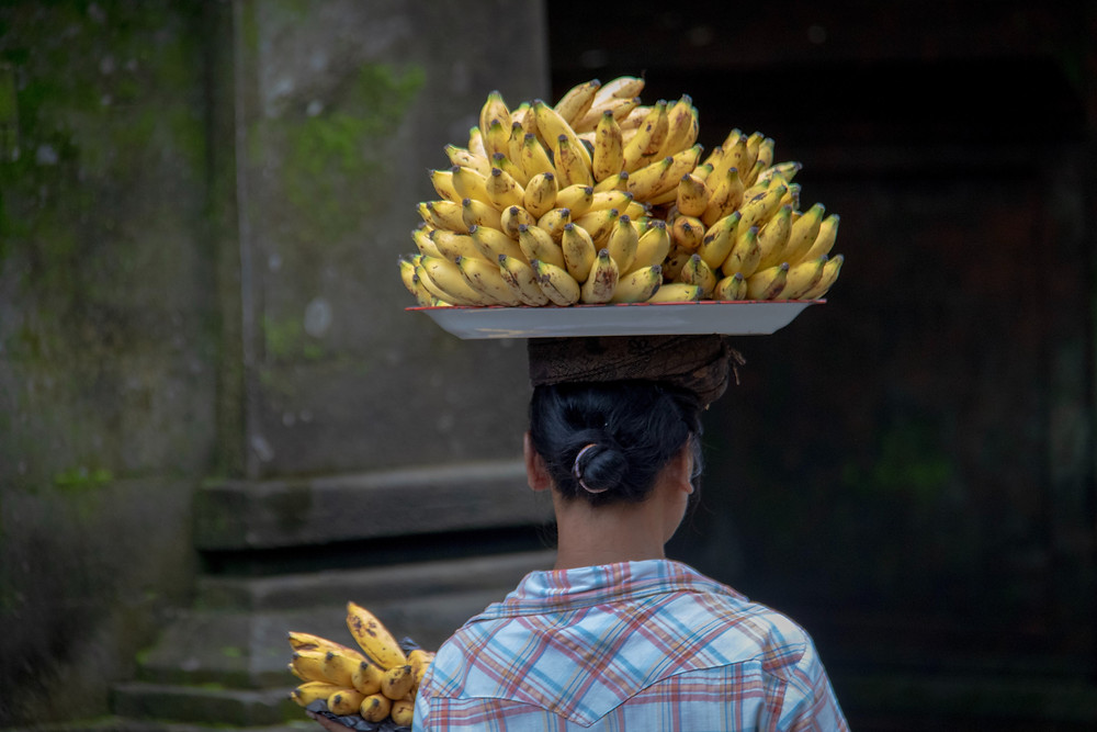 Lady carrying fruit for sale