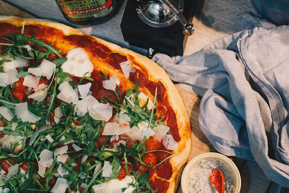 pizza italiana de rucula com tomate e lascas de queijo