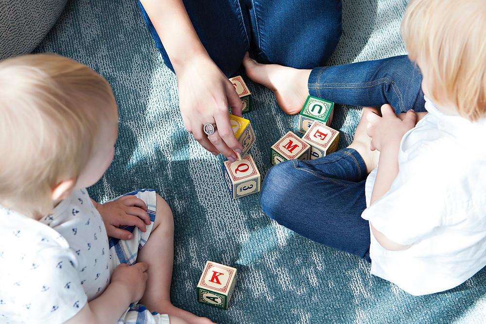 Две плави деца играат со коцки со букви со нивната бејбиситерката