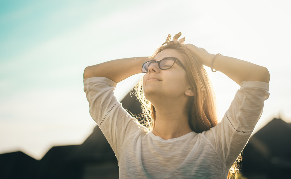 Woman holder her head and smiling while looking at the sun