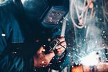 man welding frame of modular building