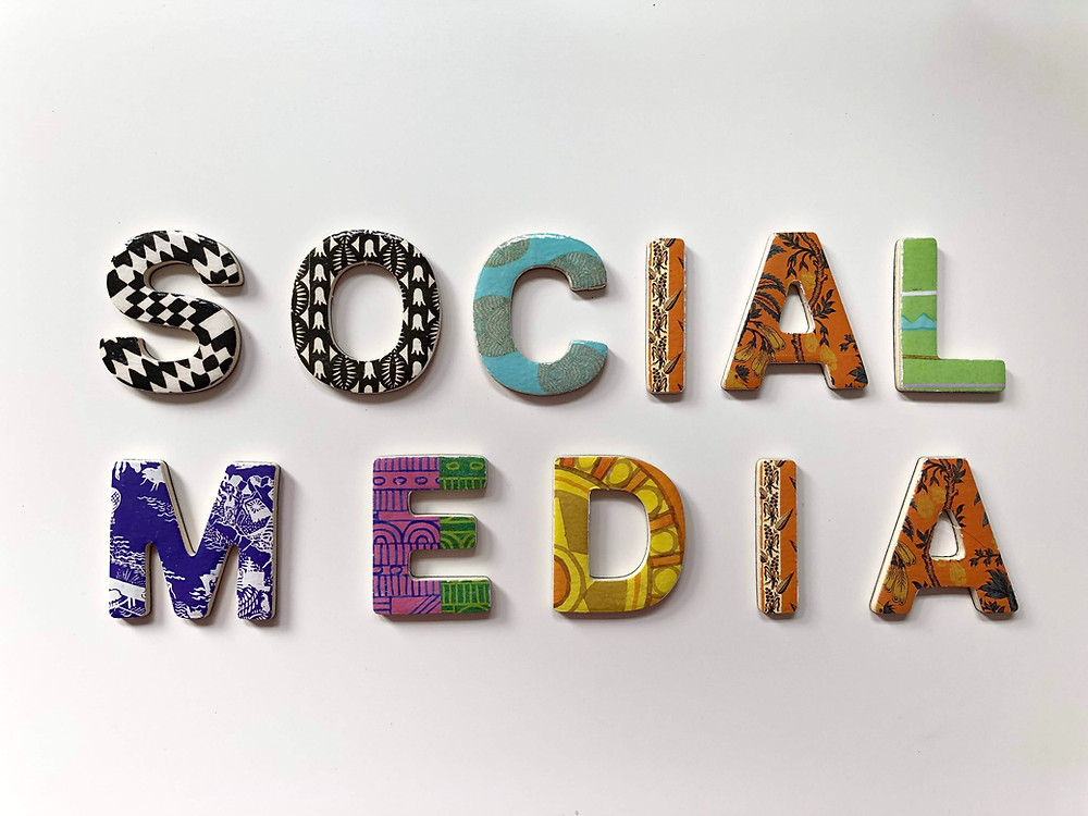 The word social media on a white background with the letters covered in different graphics.