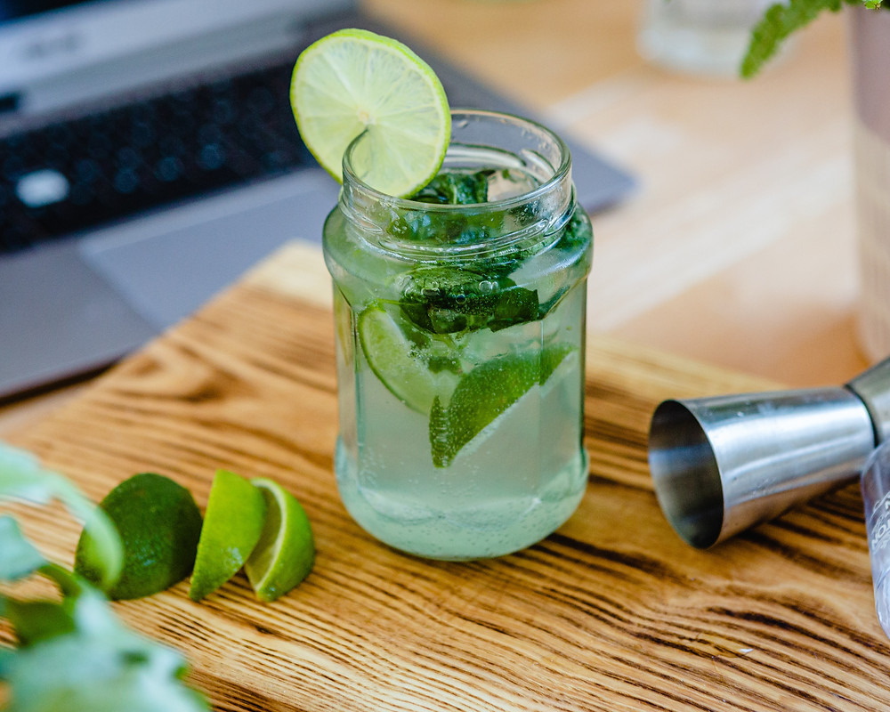 A mason jar filled with lime slices, and hazy liquid, with a round slice of lime on the lip