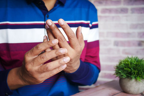 Chronic Illness Counselling - BIPOC man holding painful hands