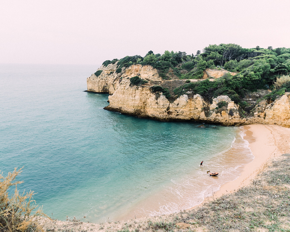 Hided bay flanked by rock formations in the Algarve, Portugal