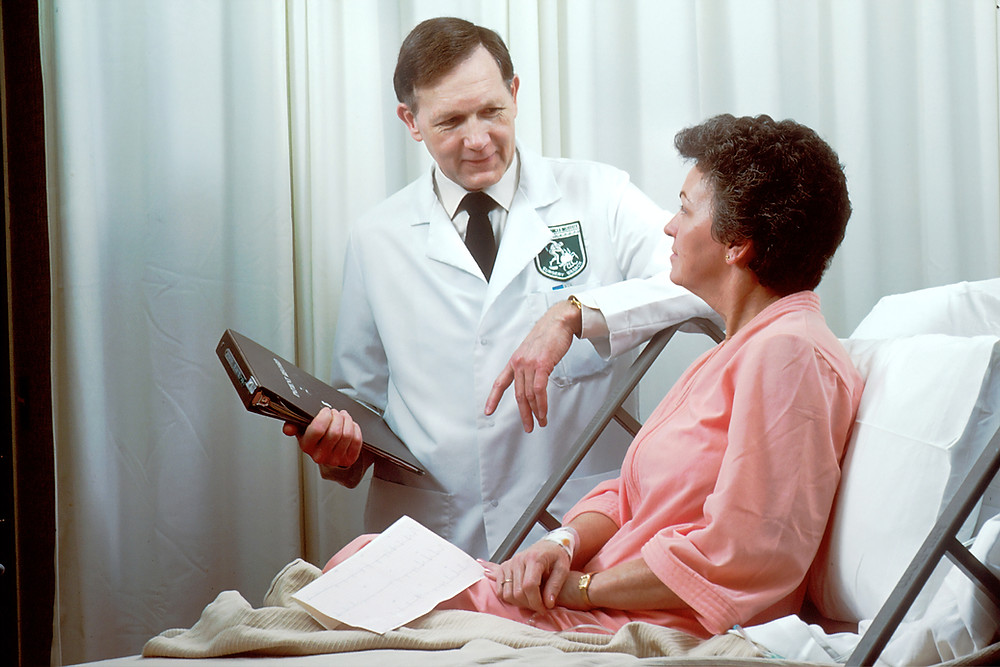 Breast cancer patient sitting on a hospital bed and asking an oncologist questions who is standing next to her.