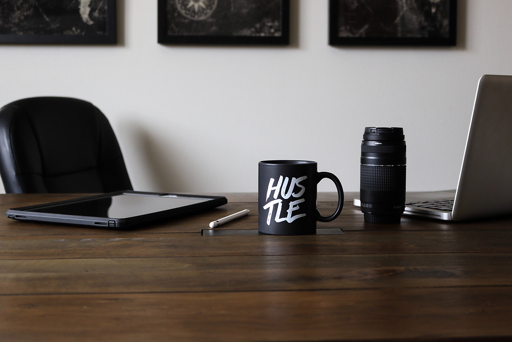 "a mug with the word ""hustle"" on a desk, next to laptop and tablet"