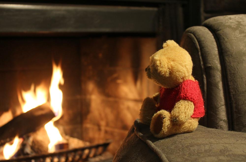 Teddy bear by a fireplace