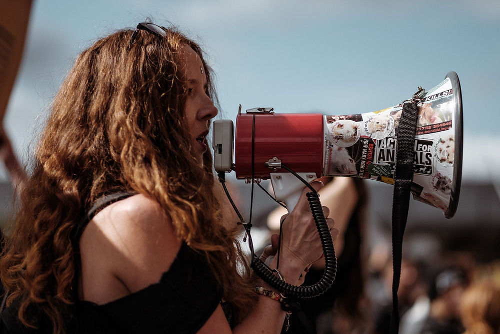 A. young person speaks through a megaphone at a protest.