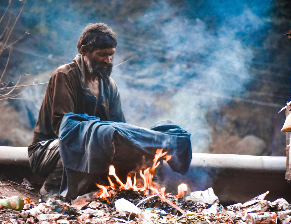 homeless man sitting by an open fire