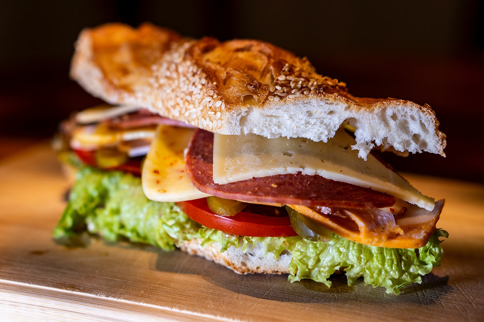 Deli sandwich stacked with meats, cheeses, tomatoes, lettuce and pickles on a rustic baguette