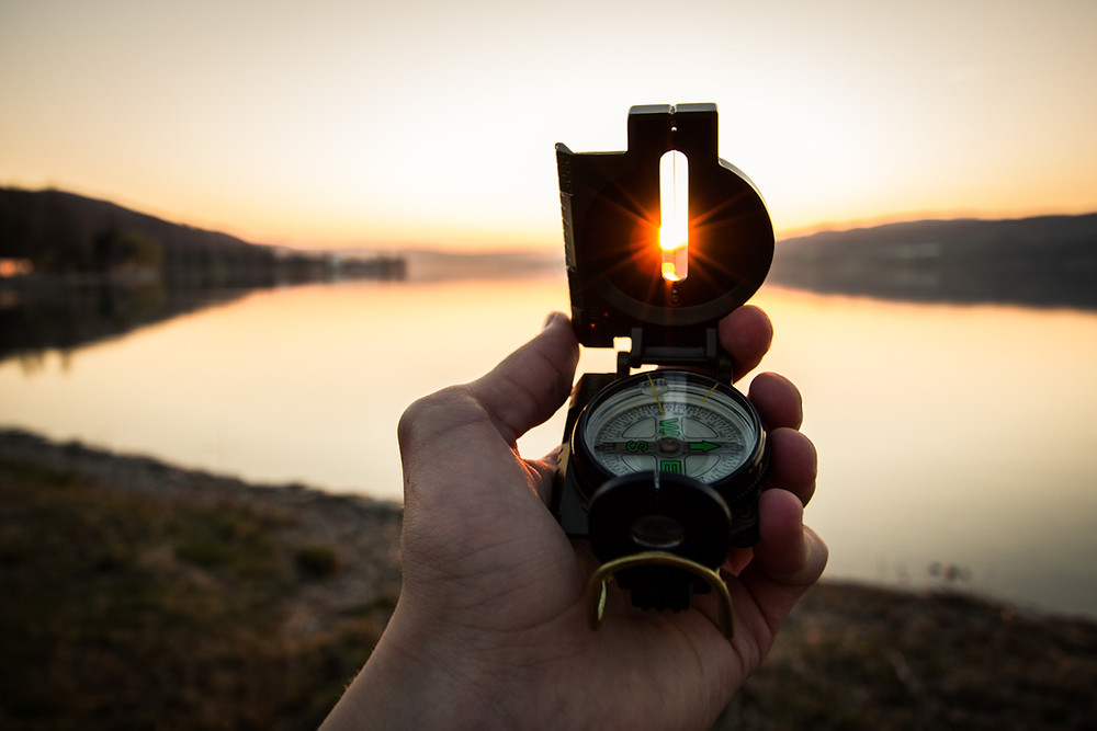 Looking at a compass in front of a lake