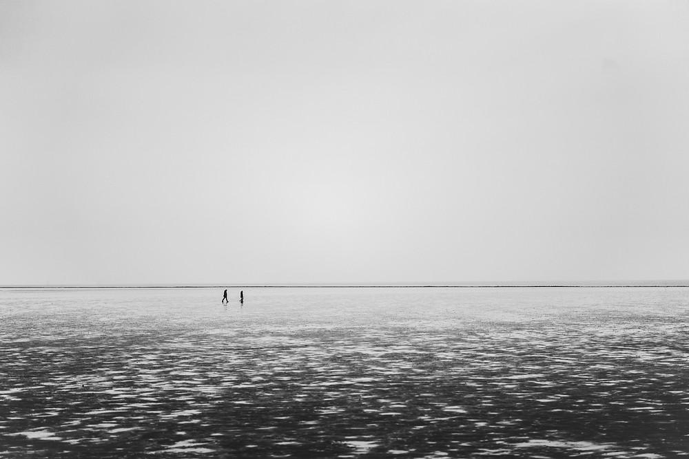 Menschen laufen am Wattenmeer