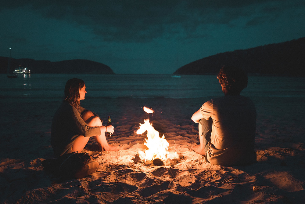 A couple sitting beside an open fire on the sand looking out to the ocean