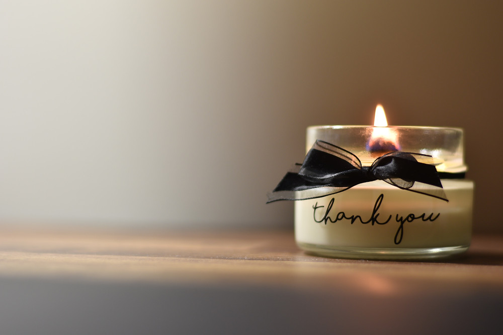 """A candle with the words """"thank you."""""""