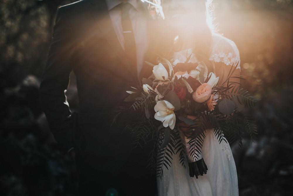Coppia di sposi in controluce ed in mezzo al verde