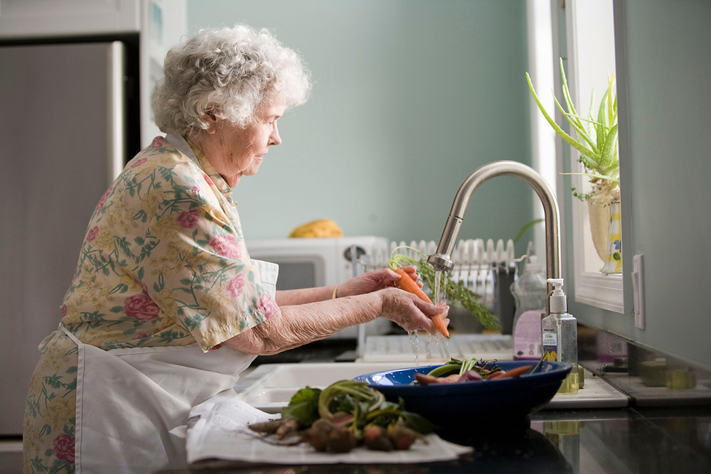 An elderly woman washes vegetables in a kitchen sink.