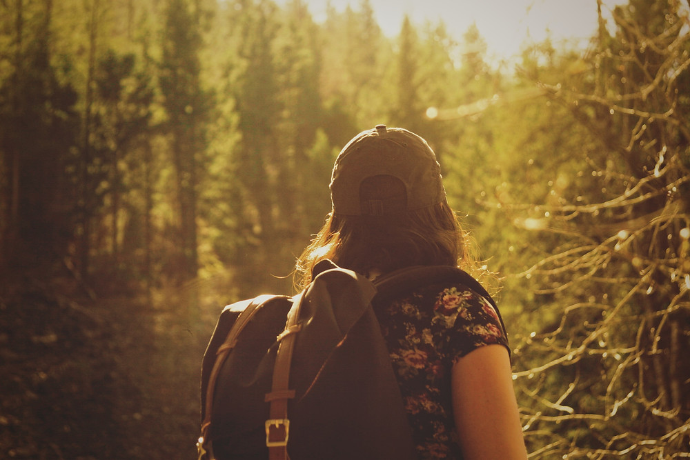 A woman with a backpack and a cap, walking through a woodland.