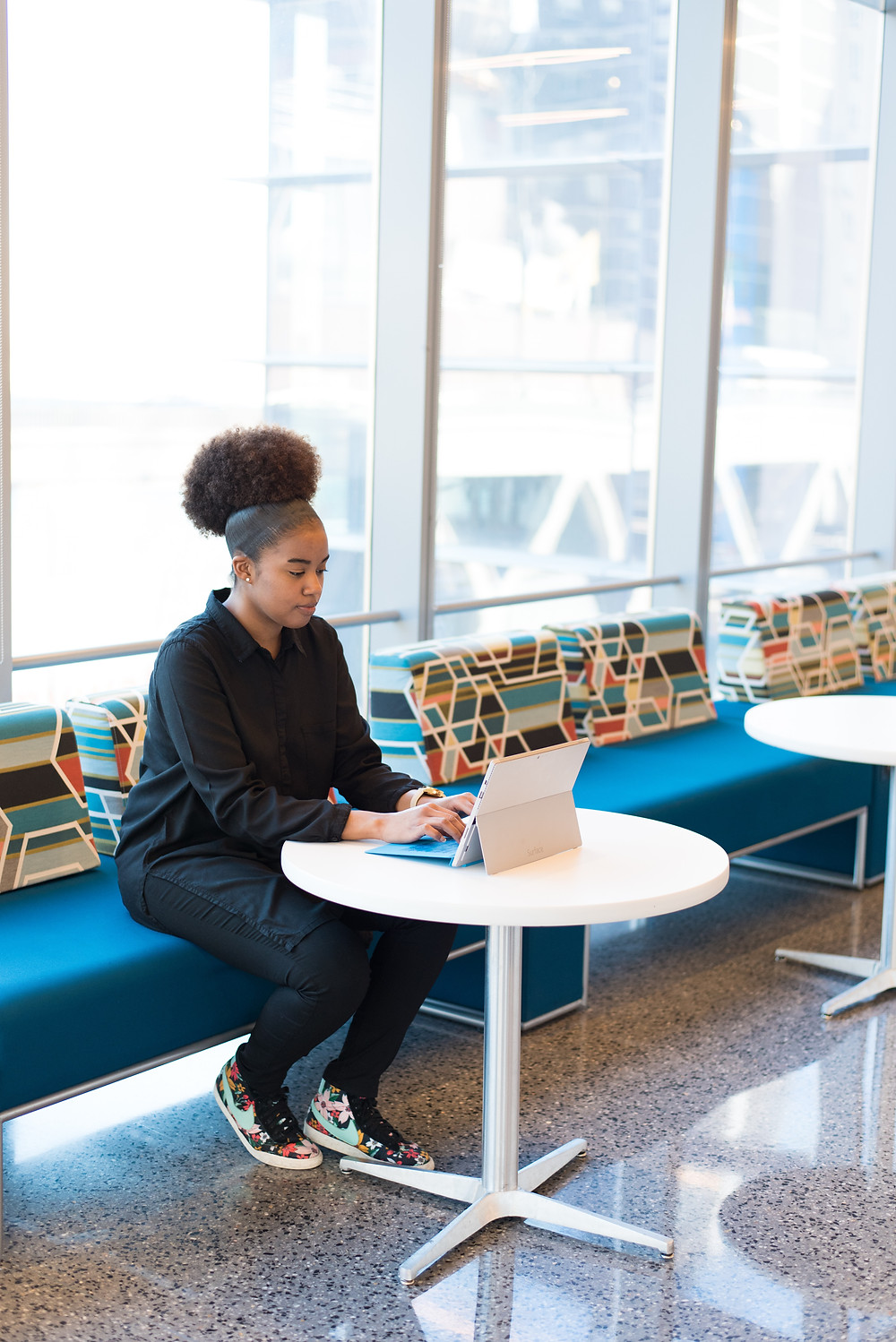 Black woman with afro puff typing on a tablet searching for postpartum anxiety symptoms