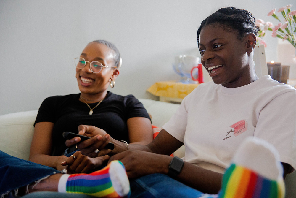 A Black couple sit on a couch watching TV together. They are wearing bright smiles and rainbow socks.