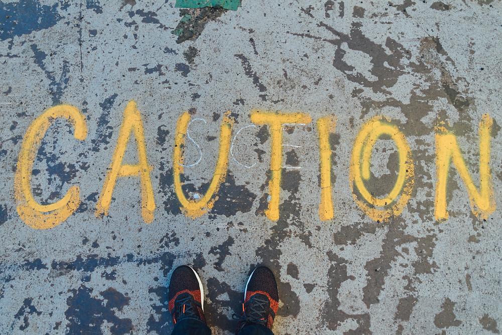 """The word """"CAUTION"""" painted onto a street"""