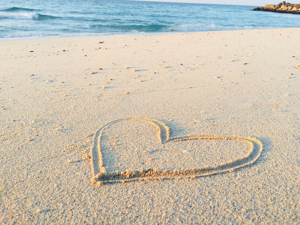Heart shape drawn in white beach sand, waves nearby.