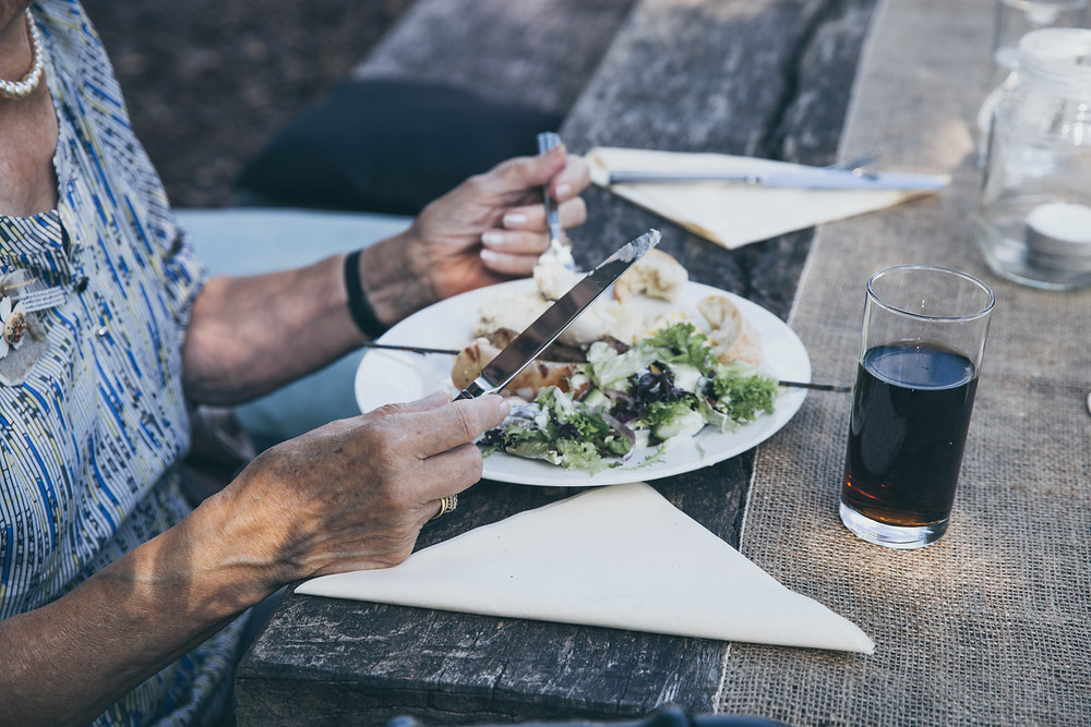 woman eating alone outside on a wooden table with white napkins