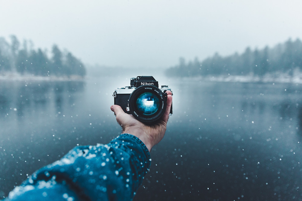 hand holding a Nikon camera by a frozen lake with snow falling
