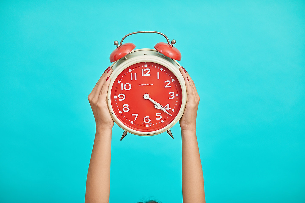 a red analogue clock held up by two hands on a blue background