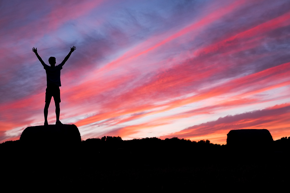 silhouette of person with open arms on mountain summit