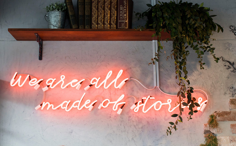 "a red neon sign on a wall saying ""we are all made of stories."""