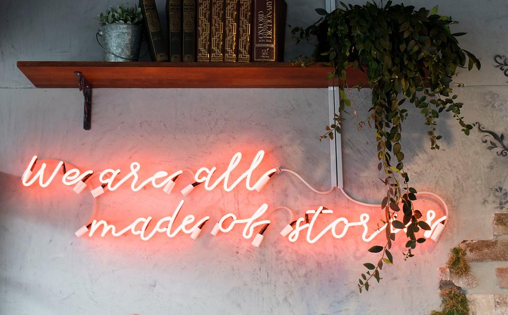 """Letrero luminoso que dice """"Todos estamos hechos de historias"""""""