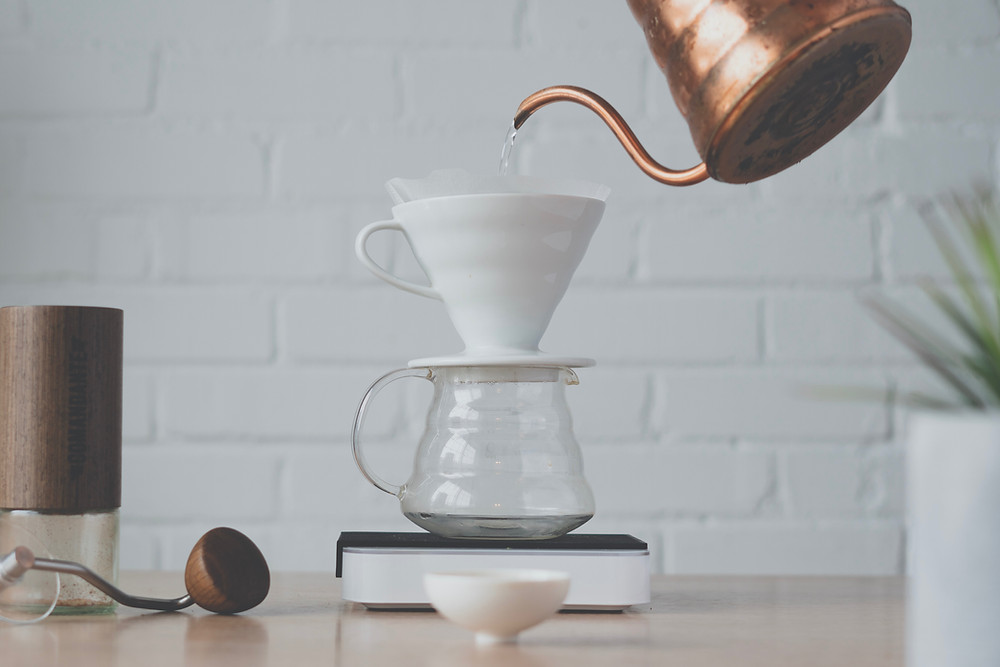 Pouring hot water from kettle to v60 dripper to make pour over coffee.