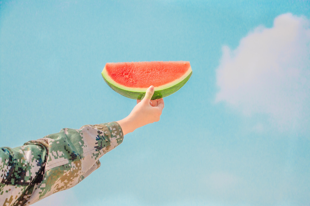 Person holding a slice of watermelon in the summer.