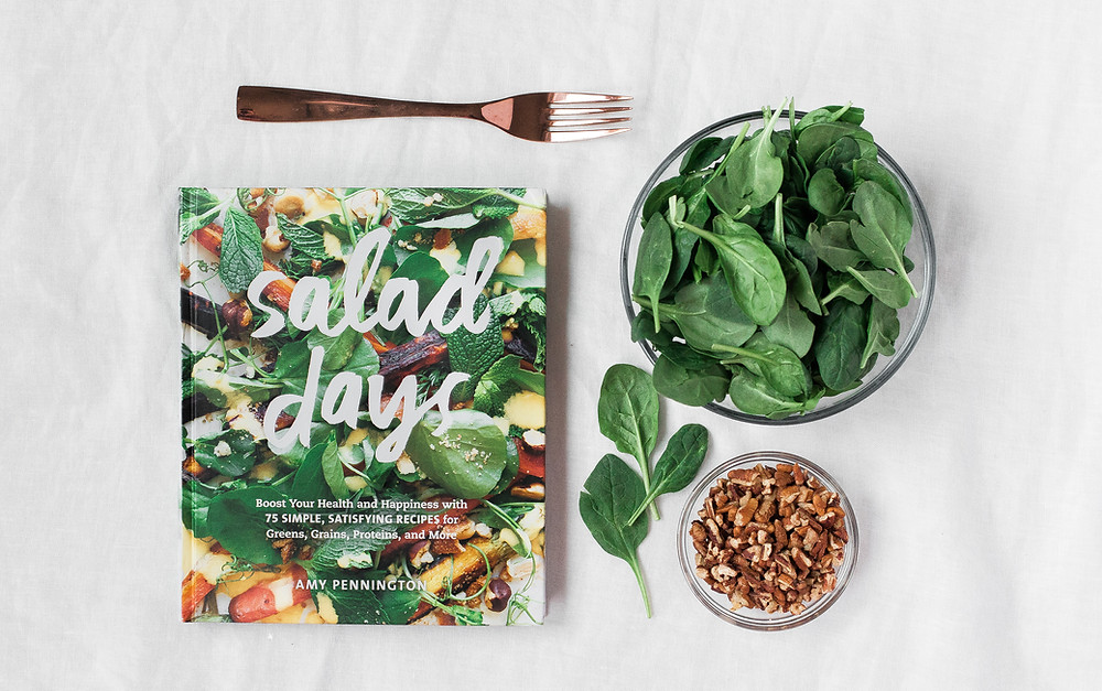 food blogger promoting a product with spinach and nuts in the bowl and a book