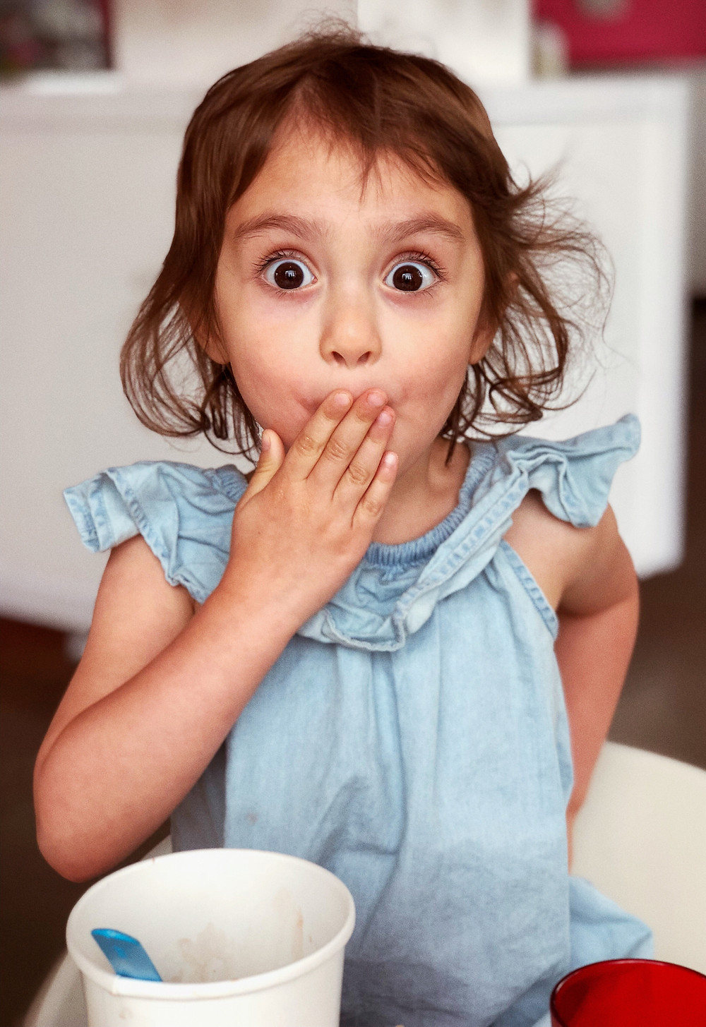 menina jovem com mao tampando a boca e olha de surpresa