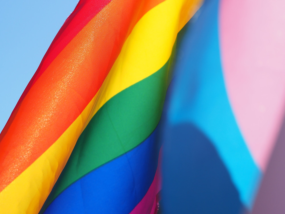 Two pride flags hang against each other on a blue background. One is rainbow for the community as a whole, the other is pink and blue for the trangender pride flag.