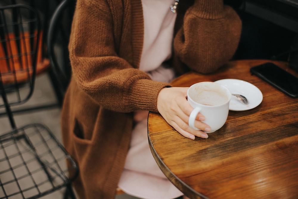 mulher segurando cafe em uma mesa de madeira