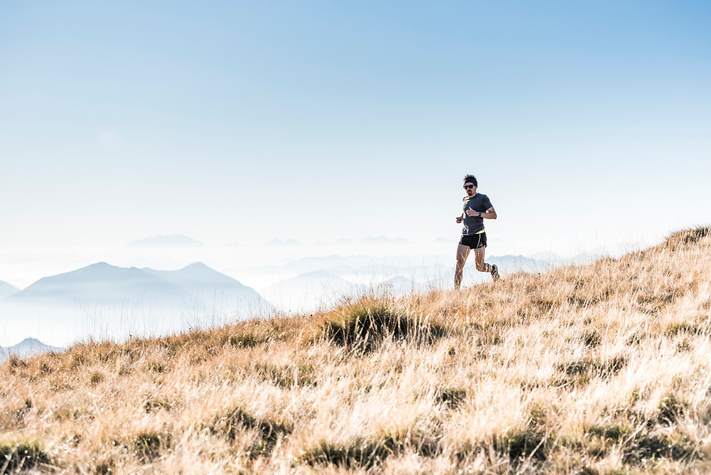 man doing steady state cardio-running in the mountains