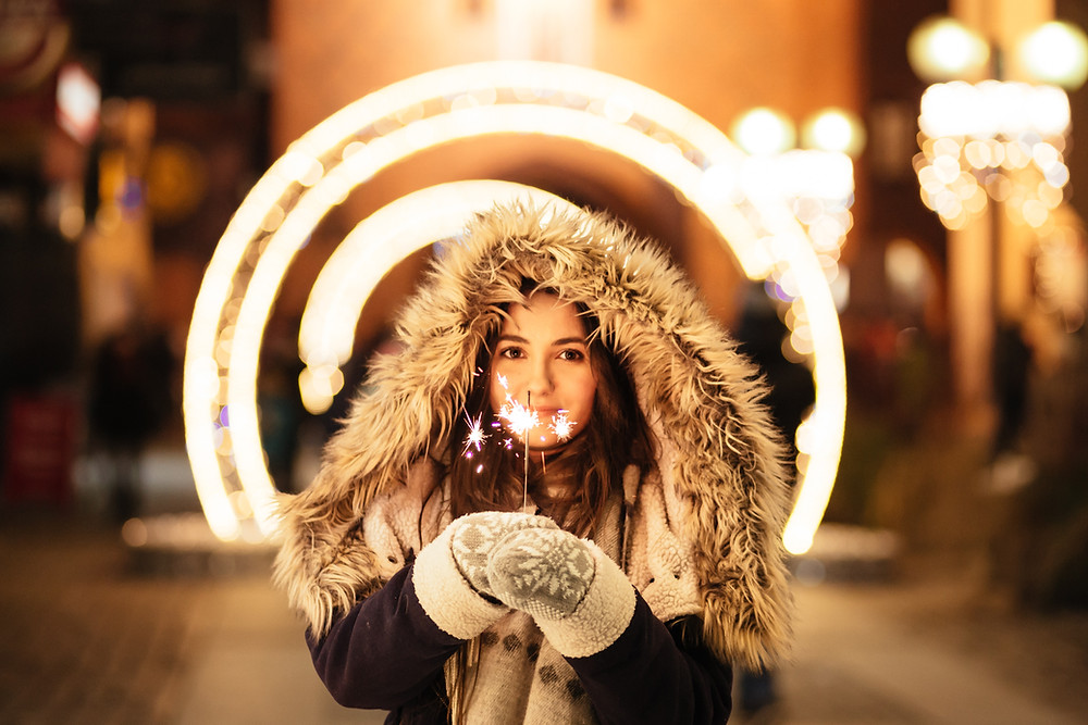 A girl in a warm coat, holding a hand-held firework.